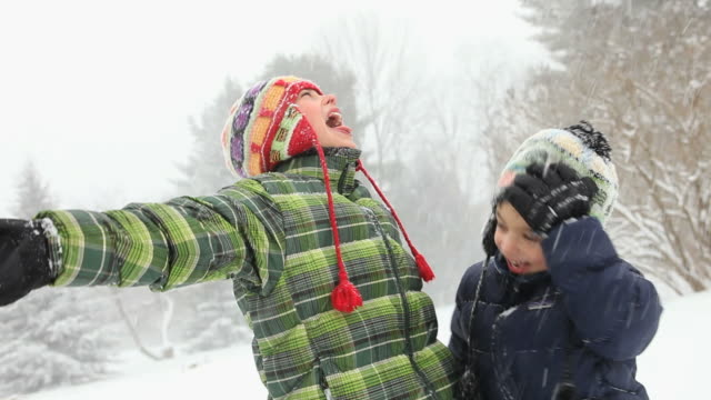 MS ZO Boys trying to catch snowflakes during snow storm / Yarmouth, Maine, USA