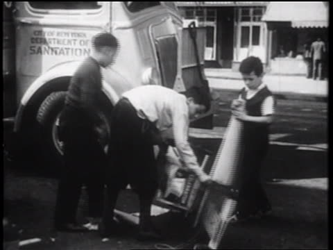 vidéos et rushes de b/w 1939 3 boys turning over scooter on city street / nyc / documentary - 1930