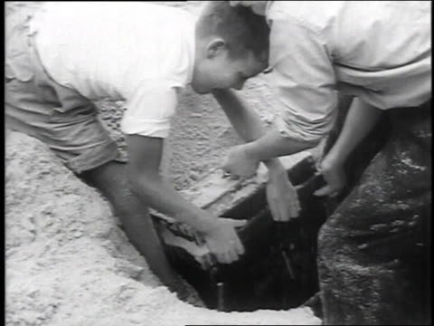 vídeos de stock e filmes b-roll de 1951 montage boys unearthing treasure box and being carried off on shoulders / egmond beach, holland - enterrado