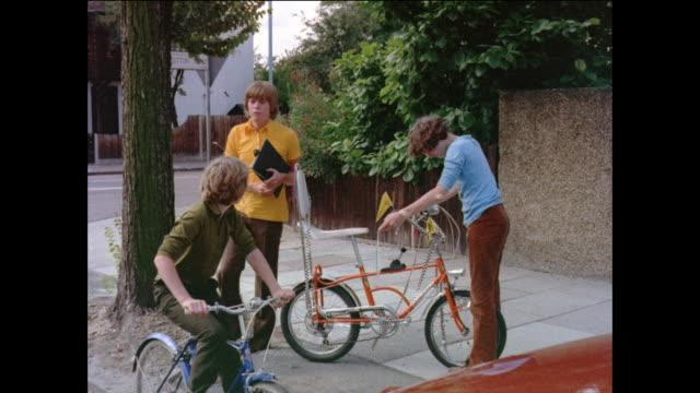 vidéos et rushes de montage boys wait for decision regarding bicycle competition disqualification / united kingdom - 1971
