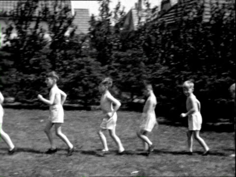 1932 b/w montage boys walking running, exercising in shorts on grass, being led by woman in white dress at children's summer camp / wyk auf fohr, nordfriesland, germany - running shorts stock videos & royalty-free footage