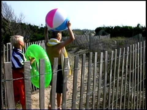 boys walking to beach - 水泳用浮き輪点の映像素材/bロール