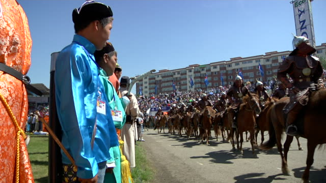 boys watching men riding horses and wearing costumes parading at naadam festival - animale da lavoro video stock e b–roll