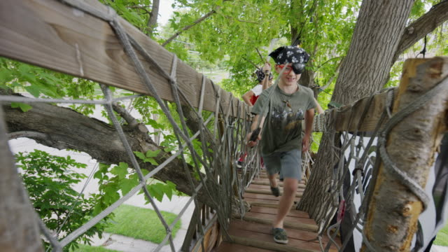 boys wearing pirate costumes running on tree bridge / provo, utah, united states - seeräuber stock-videos und b-roll-filmmaterial