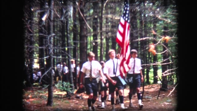 1967 boys with american flag marching through woods - all shirts stock-videos und b-roll-filmmaterial