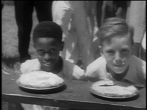 vídeos de stock e filmes b-roll de b/w 1932 pan boys with hands behind backs + pies in front of them licking lips at pie eating contest - competição