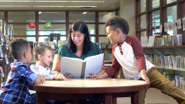boys with hispanic teacher in reading in library - preschool age stock videos & royalty-free footage