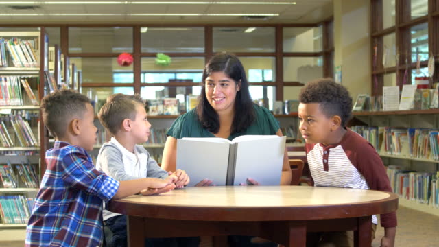boys with hispanic teacher in reading in library - 6 7 years stock videos & royalty-free footage
