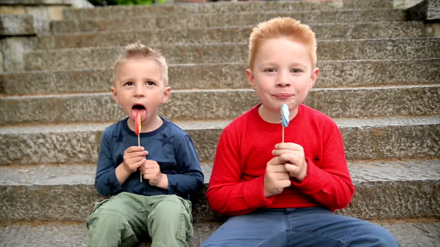 boys with lollipop. slow motion. - lollipop stock videos and b-roll footage