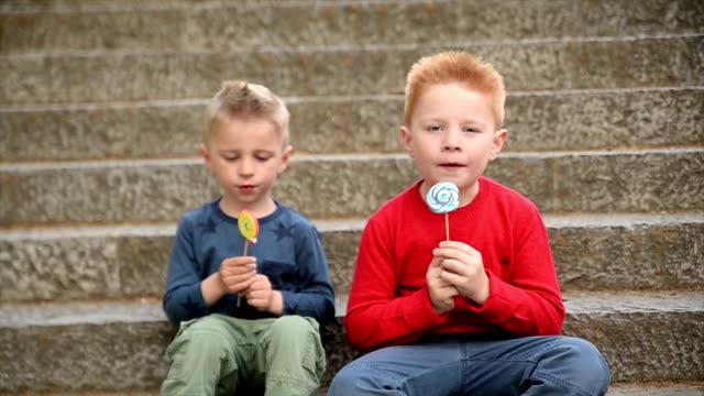 vídeos de stock, filmes e b-roll de meninos com lollipop. câmera lenta. - colocar a língua para fora