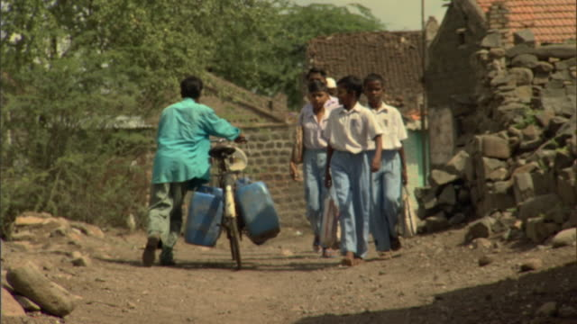 WS Boys with school bags passing adults with bicycles while walking back to village, Pune, Maharashtra, India