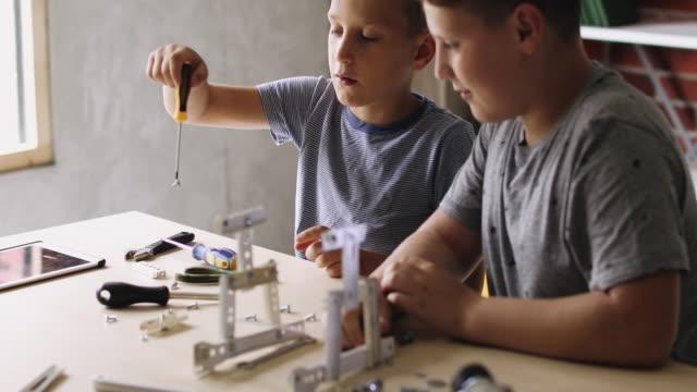 jungen arbeiten an einem schulprojekt - interaktivität stock-videos und b-roll-filmmaterial