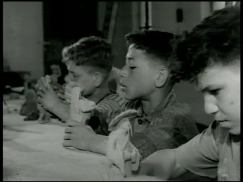 stockvideo's en b-roll-footage met boys working with clay at table boys modeling figures at table instructor w/ 'carlo' at potter's wheel. adult male hands on clay on potter's wheel... - 1946