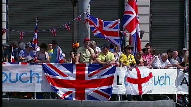 bradley wiggins becomes the first briton to win the tour de france car along british fans behind barriers with union jack flags man with 'sky'... - ツール・ド・フランス点の映像素材/bロール