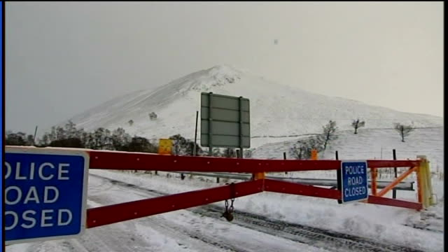 main road covered in snow - 'road closed' sign in foreground police gates closing a93 road due to snow inch: man clearing snow from roof of car with... - inch stock videos & royalty-free footage