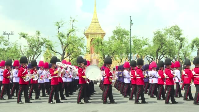 Brahmin priests drummers and soldiers in ceremonial uniforms lead a solemn but colour splashed procession through Bangkok's historic heart as...