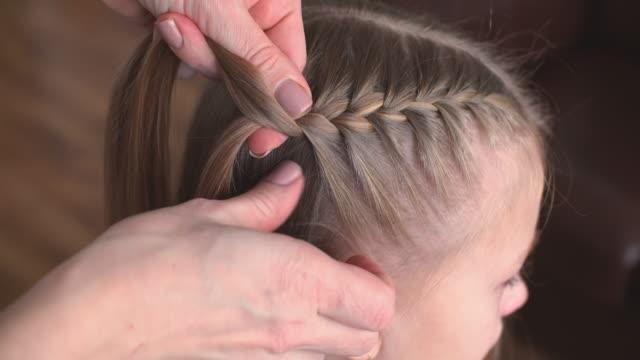 女の子のための編み込みヘアスタイル - 髪をブラシでとく点の映像素材/bロール