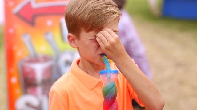 brain freeze from slushy at funfair - fanghiglia video stock e b–roll