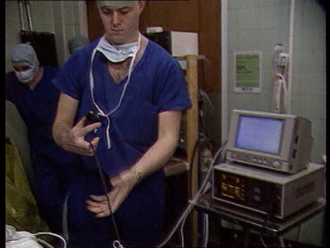 vídeos y material grabado en eventos de stock de cjd risk cr2245 itn england london st bart's hospital cms surgeons preparing patient for surgery ms assistant switches equipment on in operating... - bart