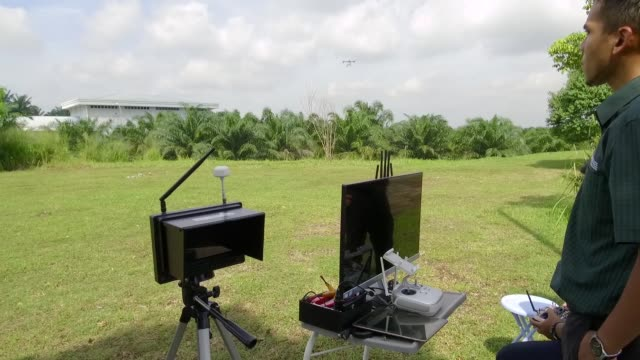 a braintree technologies sdn drone prepares to take off during a pesticide aerial spraying demonstration at a palm plantation in the universiti putra... - drone pilot stock videos and b-roll footage