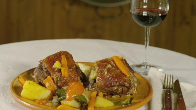 tu braised lamb, a traditional spanish dish, and a glass of wine - braised stock videos and b-roll footage