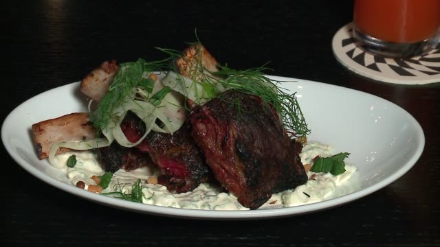 wgn braised lamb ribs served over minted yogurt and topped with fennel salad at the chicago restaurant el che on sept 22 2016 - braised stock videos and b-roll footage