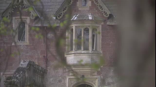 vídeos de stock, filmes e b-roll de branches frame an ornate window of the culver house in exeter, england. - janela saliente