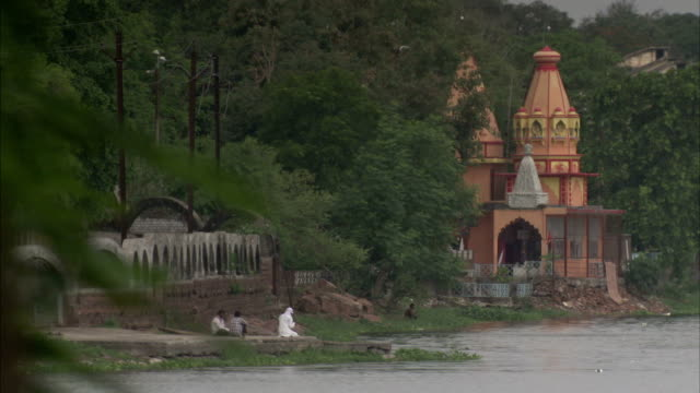 stockvideo's en b-roll-footage met branches wave in the wind near a river and two temple-like buildings. available in hd. - bhopal