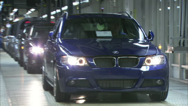 A brand new BMW drives off the assembly line in an automobile factory.