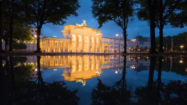 Brandenburg Gate Berlin illuminated with Reflection and Citylife Traffic Timelapse Zoom