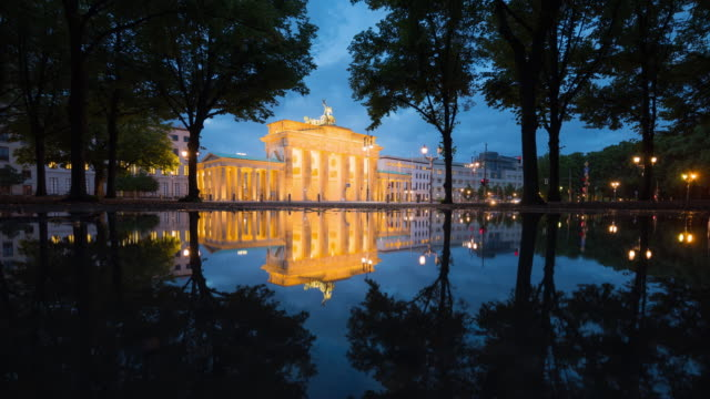 Brandenburg Gate Berlin illuminated with Reflection and Citylife Traffic Timelapse