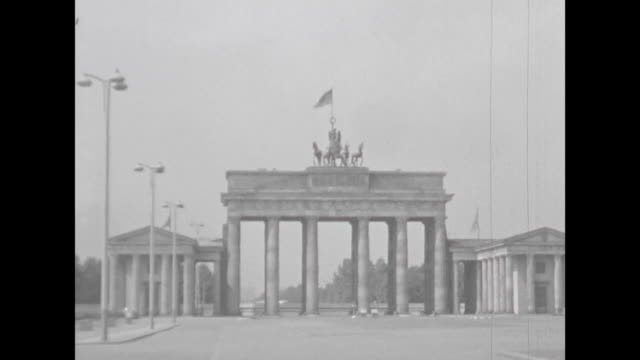 vídeos de stock, filmes e b-roll de brandenburg gate from the east panning to the reichstag building bus passing at big street different views of newly built houses typical buildings... - east berlin