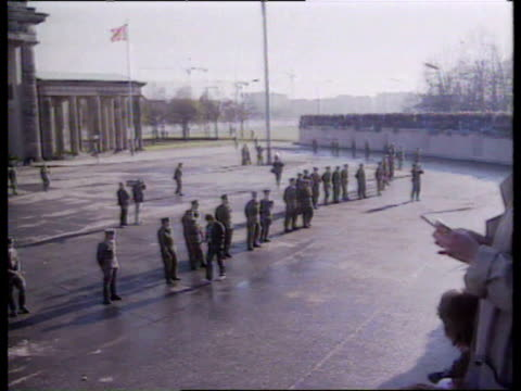 west berliner lays flowers at feet of east german border guards square in front of gate as thousands line wall chanting / west berliners singing on... - frieden stock-videos und b-roll-filmmaterial