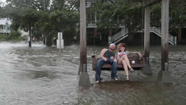 Brandon James and Brittany LaCombe sit in a swing surrounded by water from Lake Pontchartrain after the area flooded in the wake of Hurricane Barry...