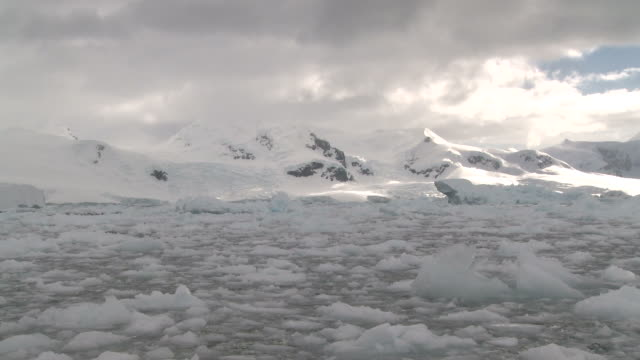 brash ice with mounains behind. neko harbour, antarctic peninsula - south pole stock videos and b-roll footage