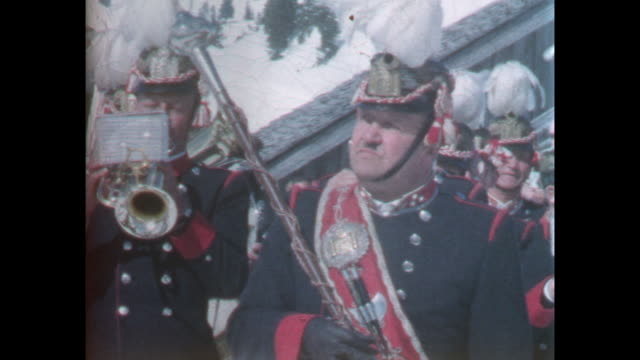 Brass band in traditional uniform playing outside at ski resort unidentified woman is filmed in closeup / 8mm amateur home movie footage filmed by...