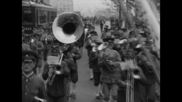 A brass band leads World War II military marchers protesting the United States and Britain citizens contribute to the war effort