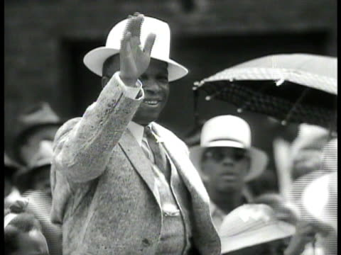 brass band players leading parade down harlem street. african american spiritual leader father divine waving to people as they pass. african american... - ブラスバンド点の映像素材/bロール