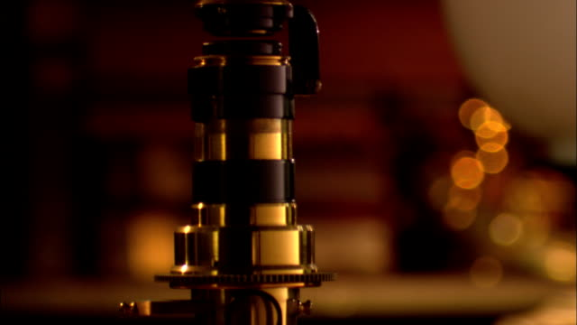a brass microscope stands on a table in a laboratory. - historische nachstellung stock-videos und b-roll-filmmaterial