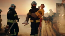 Brave Firefighter Carries Injured Young Girl to Safety where She Reunited with Her Loving Mother. In the Background Car Crash Traffic Accident Courageous Paramedics and Firemen Save Lives