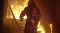 Brave Firefighter Runs Up The Stairs. In Slow Motion. Raging Fire is Seen Everywhere.
