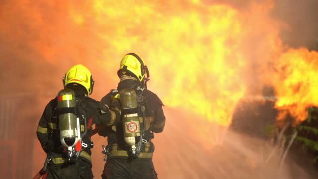 slow mo brave firefighters fighting with burning fire - släcka bildbanksvideor och videomaterial från bakom kulisserna