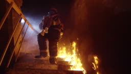 Brave Fireman Descends Burning Stairs with Saved Little Girl in His Hands. Open Flames are Seen Everywhere.
