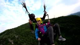 Brave woman doing tandem paragliding