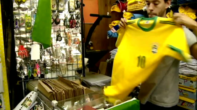 Brazil turn to psychologist ahead of quarter final INT Man in shop folding up Brazil football shirt with 'Neymar' name on back