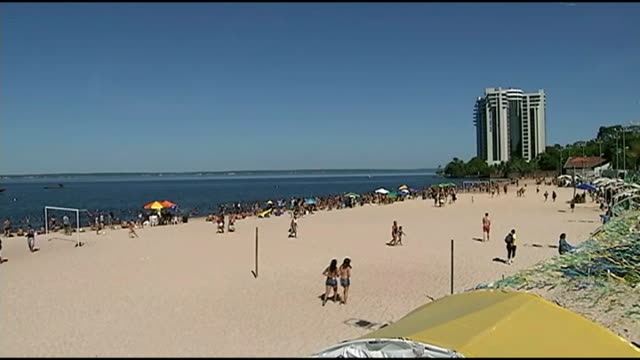 england return to rio after losing to italy brazil manaus ext general view of people on sandy beach man kicking football on beach women on beach - manaus stock videos and b-roll footage
