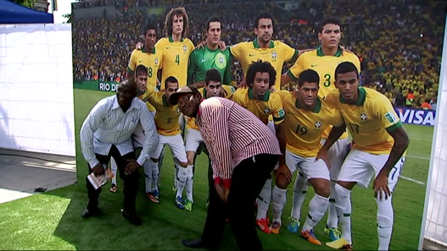 Opening ceremony / Day 1 Men posing next to giant photo of Brazilian football team Vox pops