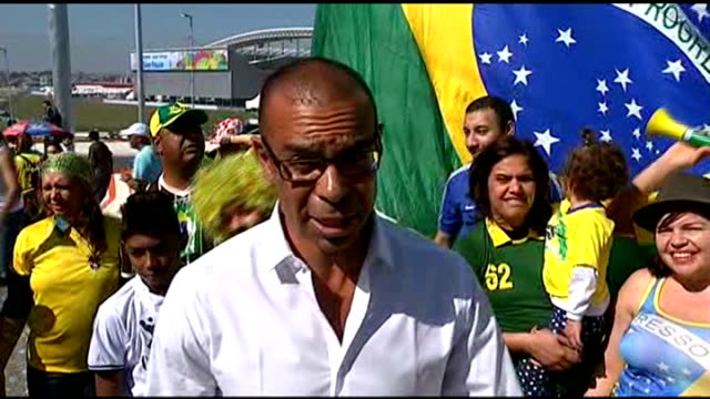 Opening ceremony / Day 1 Reporter to camera Girl waving Brazilian flag sat on man's shoulders as people sound plastic horns Men standing with thumbs...
