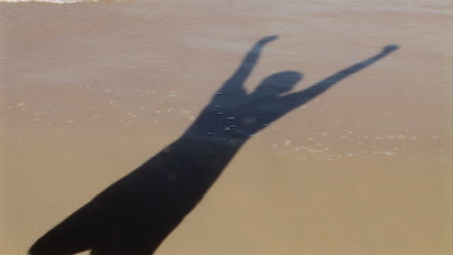 cu, brazil, bahia, shadow of person cheering on beach - unknown gender stock videos & royalty-free footage