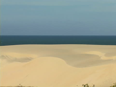 WS, PAN, Brazil, Ceara, Fortaleza, Cars driving on road through sand dunes, ocean in background